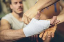 Close-up of male hands bandaging hand of boxer — Stock Photo