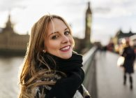 Portrait de UK, Londres, souriante jeune femme sur Westminster Bridge — Photo de stock