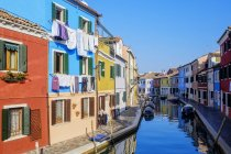 Italy, Veneto, Burano, view to colourful row of houses with drying laundry at sunlight — Stock Photo