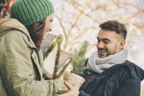Мужчина получает маленькую елку в кастрюле от женщины на Рождественской ярмарке — стоковое фото
