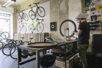 Механік працює над шин в магазині на замовлення велосипеда — стокове фото