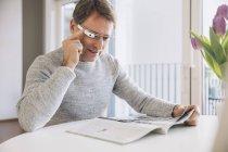 Человек с оптическим навесным дисплеем читает журнал — стоковое фото
