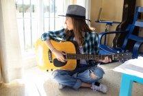 Giovane donna seduta sul pavimento a suonare la chitarra — Foto stock