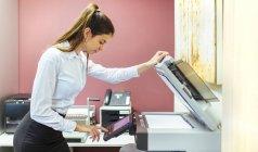 Jeune femme d'affaires travaillant à la photocopieuse dans le bureau — Photo de stock
