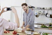 Femme prise téléphone portable photo d'homme souriant, préparer la pâte dans la cuisine — Photo de stock
