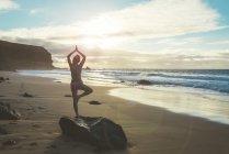Фуертевентура, Іспанія Ель місті Cotillo, назад подання жінка заняттях йогою на пляжі на заході сонця — стокове фото