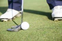 Close up de um golfista pronto para bater uma bola de golfe no verde de um campo de golfe — Fotografia de Stock