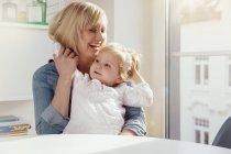 Мать и маленькая девочка обнимаются за столом — стоковое фото