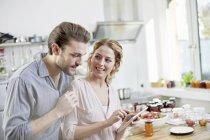 Пара, дивлячись на цифровий планшетний кухні — стокове фото