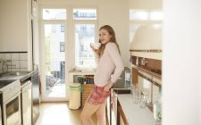 Smiling young woman standing in kitchen with bowl of coffee — Stock Photo