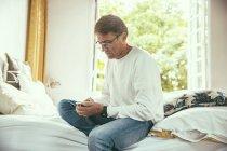 Uomo seduto sul letto a guardare il suo smartphone — Foto stock