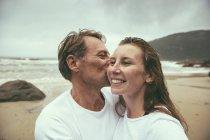 Бразилия, Флорианополис, мужчина целует женщину на пляже в дождливый день — стоковое фото