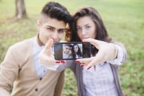 Young couple taking a selfie with smartphone at the park — Stock Photo
