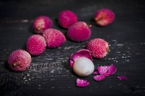 Whole and peeled lychee on dark wood — Stock Photo