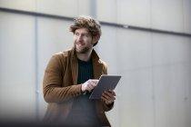 Портрет улыбающегося молодого человека с цифровым планшетом — стоковое фото