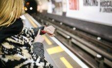 Jovem mulher olhando em seu smartwatch esperando o metrô — Fotografia de Stock