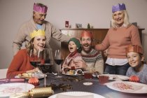 Funny three-generation family portrait with paper crowns during Christmas dinner — Stock Photo