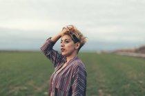 Retrato de mulher com a mão no cabelo em um campo — Fotografia de Stock