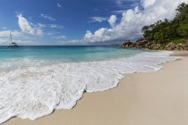 Sandy beach covered by foamy waves at Praslin, Seychelles — Stock Photo