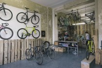 Mechanics working in a custom-made bicycle store — Stock Photo