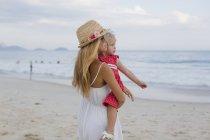 Brasil, Rio de Janeiro, mother carrying daughter on Copacabana beach — Stock Photo