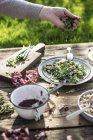 Vista potata di mano aggiungendo condimento per insalata verde con melograno, manna groppa e cipolla — Foto stock