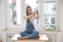 Young woman sitting on a table at home taking selfie with smartphone — Stock Photo