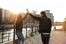 Germany, Berlin, young walking along River Spree high fiving — Stock Photo