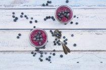 Дві склянки Чіа і лохини пудинг і дві ложки по дереву — стокове фото