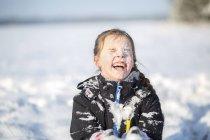 Retrato de muchacha que ríe con la cara cubierta de nieve - foto de stock