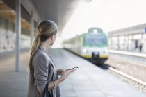 Businesswoman with cell phone on station platform looking at incoming train — Stock Photo