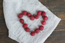 Heart shaped with fresh raspberries — Stock Photo