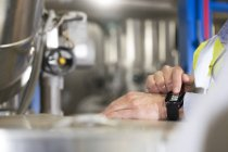 Close-up of male hands using smartwatch in industrial plant — Stock Photo