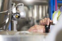 Крупный план мужских рук с помощью умных часов на промышленном предприятии — стоковое фото