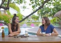 Dos mujeres felizes sentado en la mesa en la piscina hablando - foto de stock