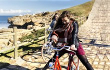 Two happy young women riding bicycles along path — Stock Photo