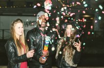 Enthusiastic friends having a party outdoors at night — Stock Photo