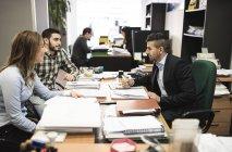 Клерк, помогая молодая пара с документами в офисе — стоковое фото