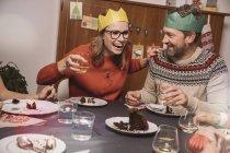 Casal feliz com coroas de papel rindo enquanto o jantar de Natal — Fotografia de Stock
