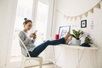 Frau mit Handy zu Hause — Stockfoto