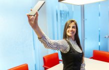 Portrait of smiling businesswoman taking selfie with smartphone in a conference room — Stock Photo