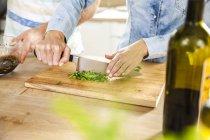 Chopping herbs on chopping board — Stock Photo