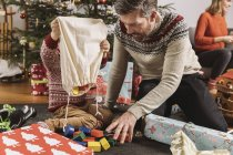 Father and son playing with building bricks in front of Christmas tree and mother on background — Stock Photo
