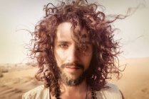 Homme aux cheveux bouclés debout dans le désert — Photo de stock