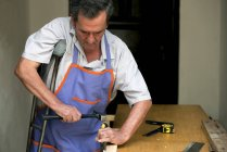 Senior man with crutch working at workbench — Stock Photo