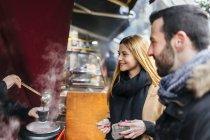 Giovane coppia acquisto di vin brulè al mercato bancarella — Foto stock