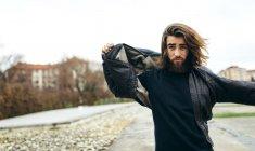Ritratto di giovane uomo barbuto che mettendo il suo giubbotto di pelle — Foto stock