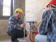 Plumbers working on construction site — Stock Photo