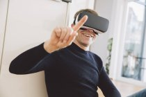 Smiling man wearing virtual reality glasses pointing his finger — Stock Photo