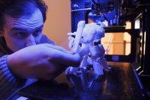 Homme examinant une figure de robot imprimée par une imprimante 3D — Photo de stock